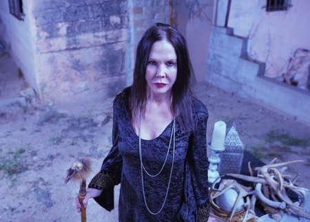 priestess: Scary priestess with fetish standing near altar