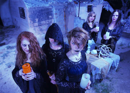 priestess: Coven of five witches outdoors holding candles Stock Photo