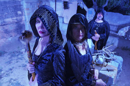 priest's ritual robes: Group of three witches in black robes near altar outdoors Stock Photo