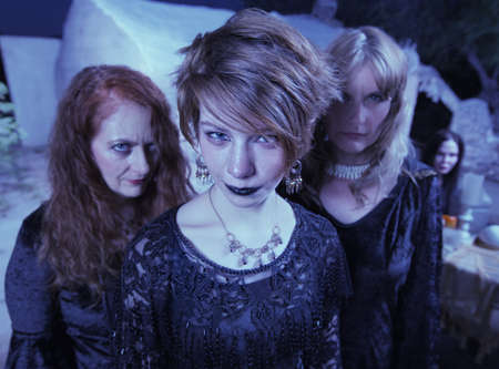 wicca: Three beautiful women in black standing together outdoors