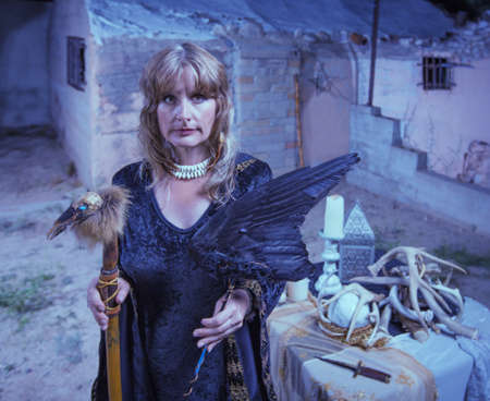 fetishes: Serious female witch with altar and fetishes