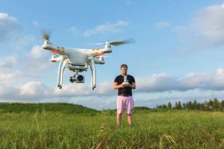 Persoon in het veld beheersen van drone met camera
