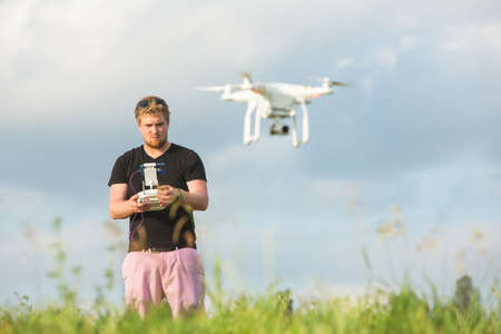 surveillance camera: Man outdoors with remote control and flying surveillance drone