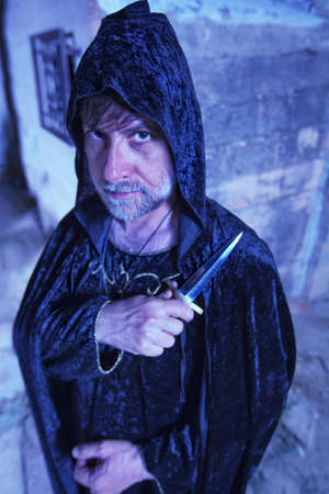 cloak and dagger: Serious male warlock in cloak with dagger