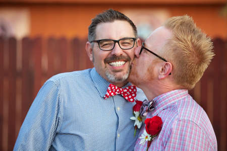 adult sex: Smiling man with eyeglasses being kissed by spouse