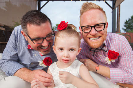 adult sex: Smiling gay couple with daughter sitting outdoors Stock Photo