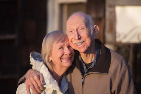 senior citizen: Grinning older couple embracing while standing outdoors