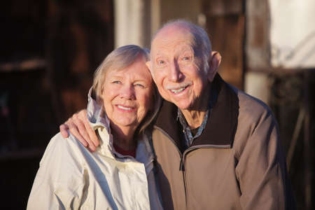senior citizen: Cute elderly Caucasian couple in jackets smiling outdoors