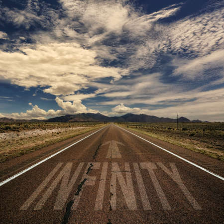 infinity road: Conceptual image of desert road with the word infinity and arrow Stock Photo