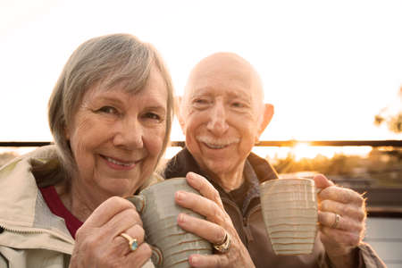 mujeres ancianas: Alegre pareja mayor sentado al aire libre con café Foto de archivo