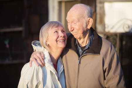 Cute European senior couple outdoors looking at each other