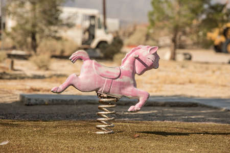 playground ride: Disused toy horse ride on derelict playground