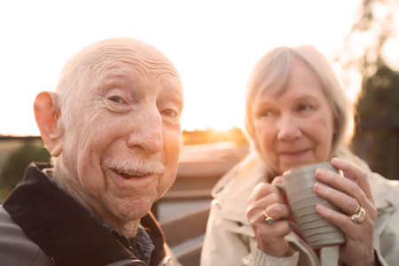 jokes: European senior couple together outdoors making jokes