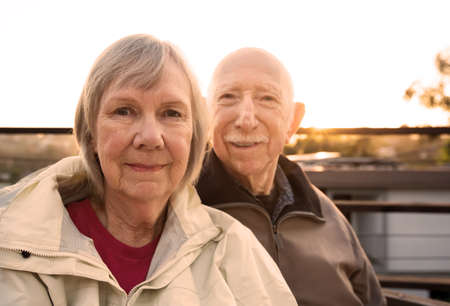 grinning: Grinning Caucasian senior couple in jackets sitting outdoors Stock Photo