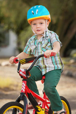 single child: Single child in helmet riding a bicycle Stock Photo
