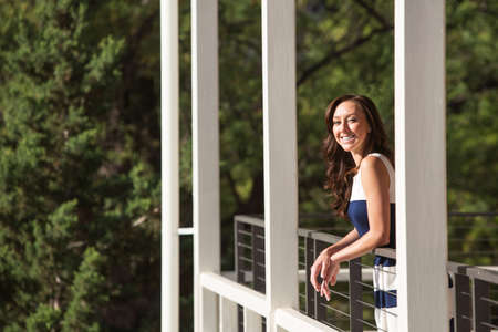 balcony: Single female adult standing on balcony outdoors Stock Photo