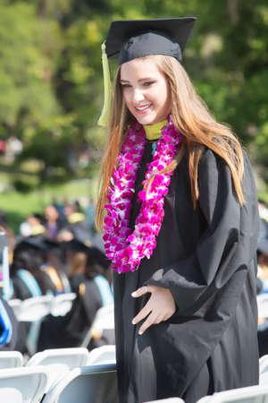 toga y birrete: Graduado de la universidad feliz caminando entre las sillas al aire libre
