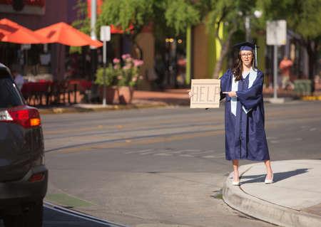 toga y birrete: Graduado de pie en la calle con la ayuda signo