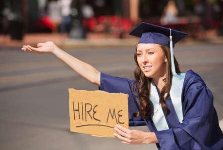 Einzelne Hochschulabsolvent im Kleid holding mich anstellen Zeichen