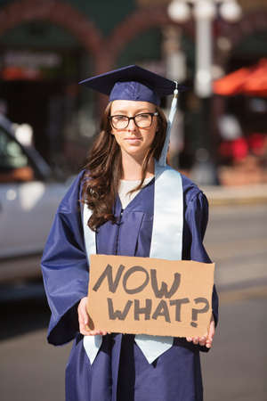ambiguity: Uncertain college graduate in blue holding cardboard sign Stock Photo