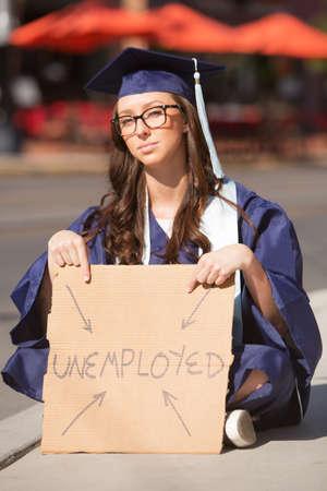 Alleenstaande werkloze jonge vrouwelijke afgestudeerde zitten met teken