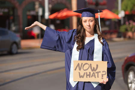 hand out: Serious female student holding hand out with cardboard sign Stock Photo