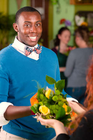 SATISFIED: Satisfied customer in a busy flower shop being handed a bouquet Stock Photo