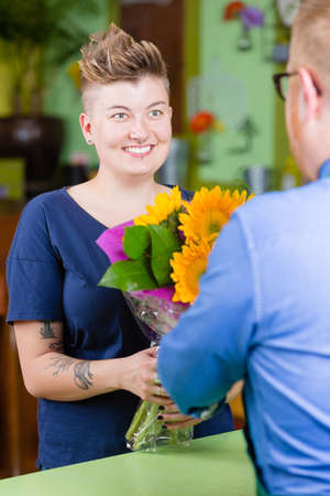 Woman buying sunflowers at a florist shop Imagens