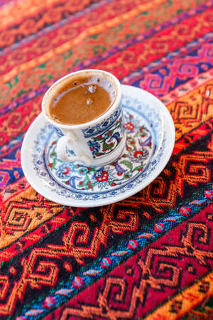 Turkish style coffe in traditional small cup on colorful background