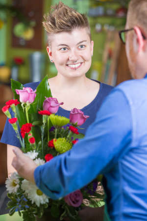 spiked hair: Attractive woman buying arrangement at a florist shop