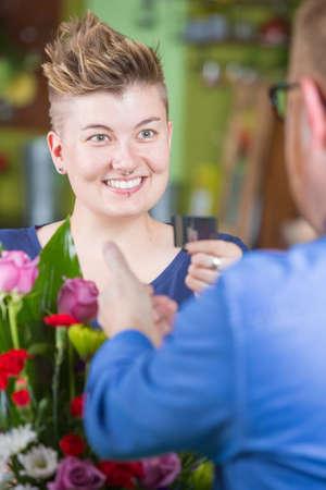 spiked hair: Cute female customer in flower shop using credit