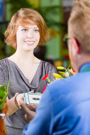 purchase: Smiling customer in a busy flower shop using electronic coupon