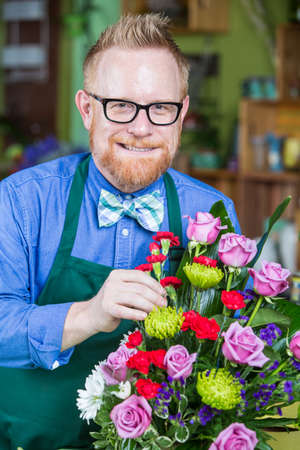 dapper: Dapper man wearing eyeglasses and apron creating a flower arrangement Stock Photo