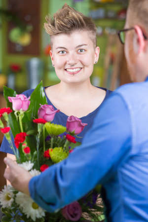 spiked hair: Smiling woman buying arrangement at a florist shop Stock Photo