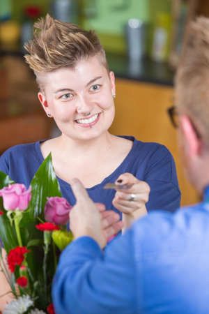 spiked hair: Smiling female customer in flower shop using credit