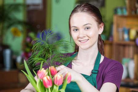 mujer sola: Joven y bella mujer en el delantal verde crear un arreglo de tulipán