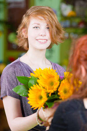 red haired girl: Teenage red haired girl buying sunflowers at a florist shop