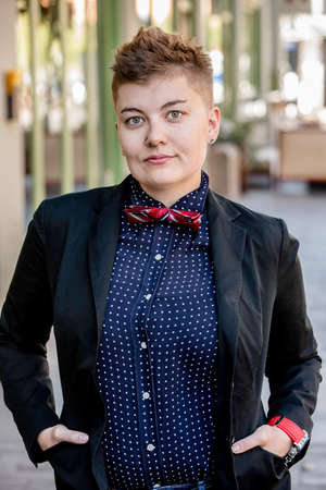 dapper: Serious dapper young gender fluid woman on city sidewalk