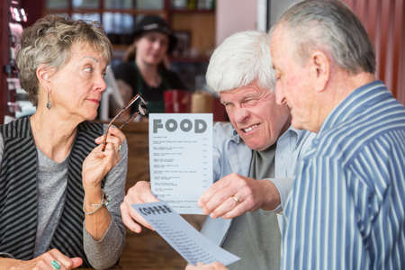 farsighted: Mature man has difficulty reading menu in a cafe