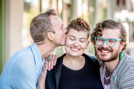 homosexual partners: A kiss among attractive gender fluid friends Stock Photo