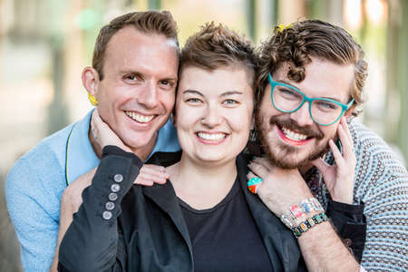Three gender fluid friends pose and smile Stockfoto