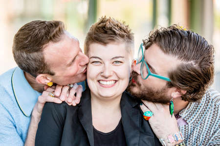 Two gender fluid young men kiss their cute female friend Banque d'images