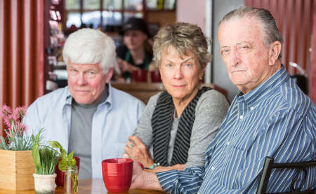 skeptical: Skeptical mature friends in a coffee house Stock Photo