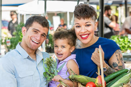 produces: Smiling family with basket of produce at farmers market