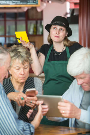 Mature friends in a coffee house distracted by their devices as server waits Imagens - 116796859
