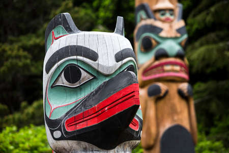 tlingit: Totem Guard at Saxman Village with Beaver pole in background Stock Photo