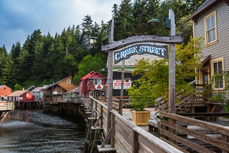 relying: KETCHIKAN, AK - MAY 15: Current businesses relying on tourism occupying historic buildings on Creek Street on May 15, 2016 in Ketchikan, AK.