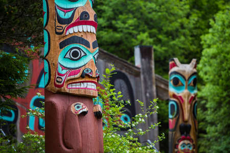 tlingit: Detail of totem pole at Saxman Village tribal house near Ketchikan Alaska with Sun Raven in background