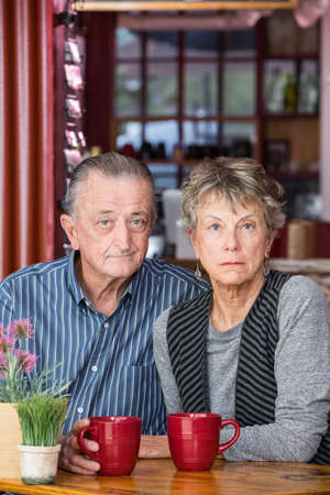 business concern: Serious mature couple sitting next to each other in a coffee house