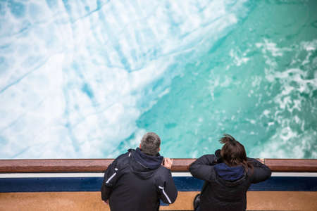 cruise travel: Two passengers at ship railing viewing glacial ice in the Endicott Arm near Juneau